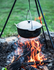 Cooking in the open-air. Cauldron over the campfire.