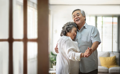 Cheerful Asian Senior couple dancing and smiling.