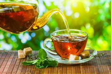 Tea time. Pouring out hot tea into a cup. Green nature background.