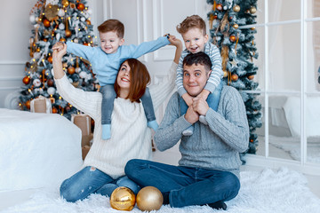 A family of four hugging in front of the christmas tree. New year's eve. Cozy holiday at the fir-tree. love, happiness and big family concept