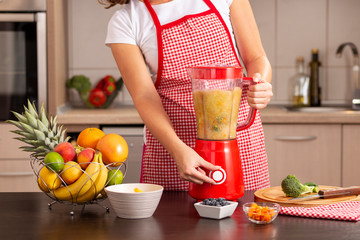 Woman turning on the blender