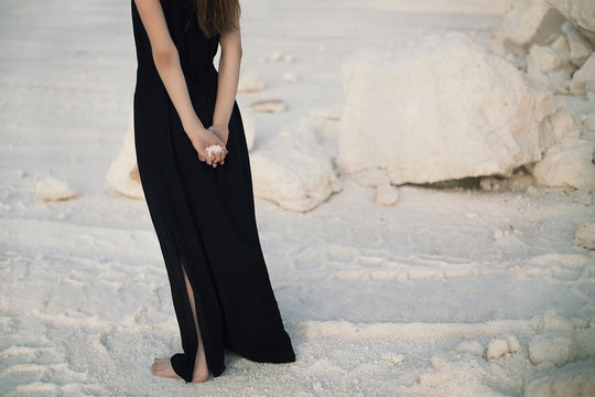 Crop woman standing on sand
