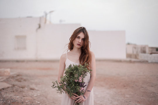 Portrait of young brunette woman holding bouquet outdoors