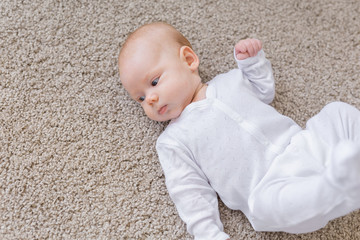Baby, infant and childhood concept - Top view of the child on the floor
