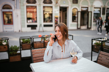 Smiling woman talking on the phone in outdoors cafe.