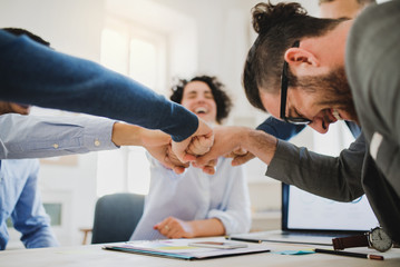 Young businesspeople sitting around table in a modern office, making fist bump.