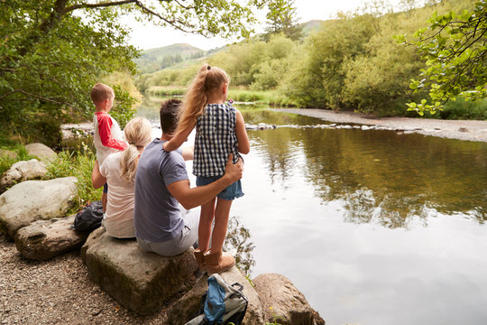 Family On Hike Looking Out Over River In UK Lake District