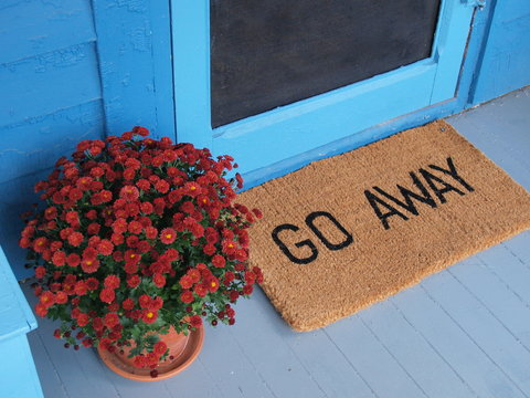 Unwelcoming welcome mat says Go Away on a pretty porch