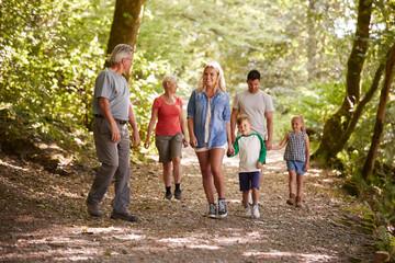 Multi Generation Family Enjoying Walk Along Woodland Path Together
