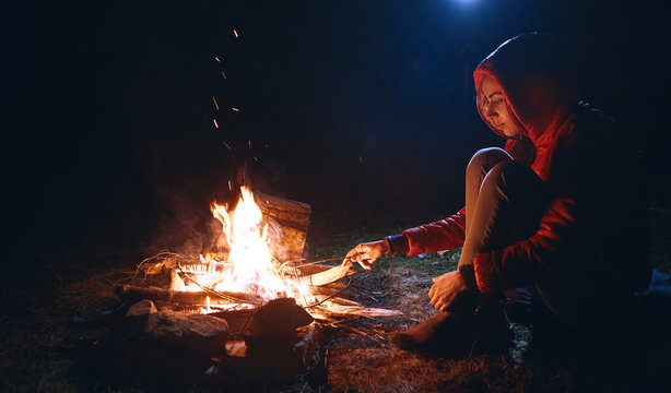 Young woman in sitting near the campfire at cold night