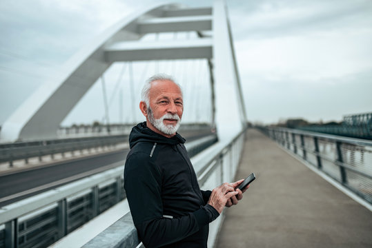 Portrait of a senior in sportswear text messaging outdoors, on the city bridge.