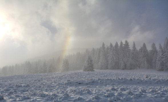 Scenic winter mountain landscape with rainbow. Winter wolderland.