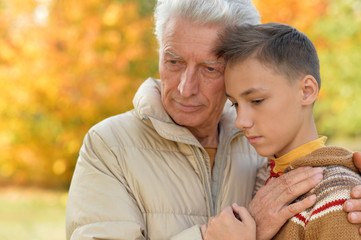 Portrait of sad grandfather and grandson hugging in park
