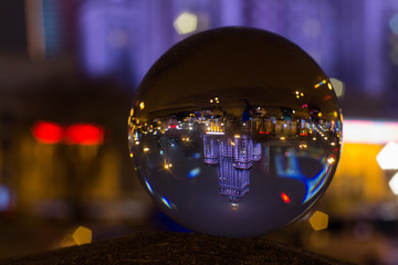 Palace of Culture and Science Warsaw - captured flipped reflection in crystal ball at night in rainy autumn time.