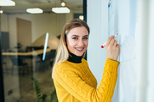 Young businesswoman writing on white board. Looking at camera.