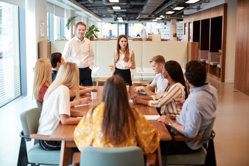Businessman And Businesswoman Addressing Group Of Young Candidates Sitting Around Table And Collaborating On Task At Graduate Recruitment Assessment Day