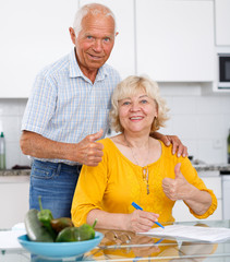 Mature couple at kitchen table filling up documents