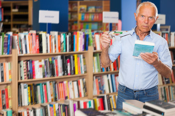 elderly male customer visiting bookshop in search of interesting fiction