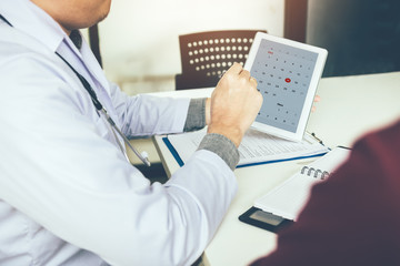Doctor holding tablet and pointing on calendar appointment reminder to patient.