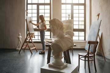 Artist at the working process. Young woman creating the painting. Workshop room with light and classical sculpture busts