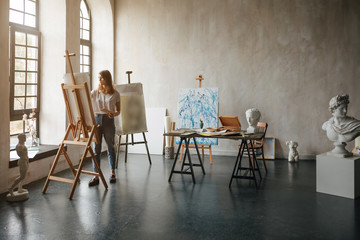 Artist at the working process. Young woman creating the painting. Workshop room with light and classical sculpture busts. Inspiretion atmosphere mood. Backlight