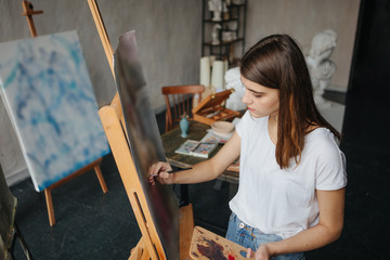 Artist painter young beautiful girl. Working creating process. painting on easel. inspired work