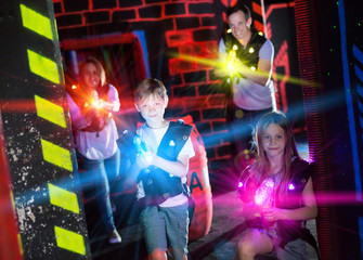 Brother and sister playing laser tag in beams