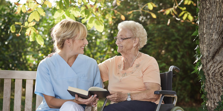 Carer reads a book to the elderly person