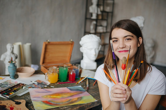 Adorable young artist girl holding brushes and smiling. Creative workshop room at the background