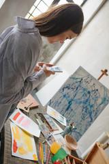 Artist internet blogger taking photos of work. Workshop inspiration mood. Backlight. Vertical composition.