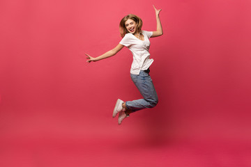 happiness, freedom, motion and people concept - smiling young woman jumping in air over pink background