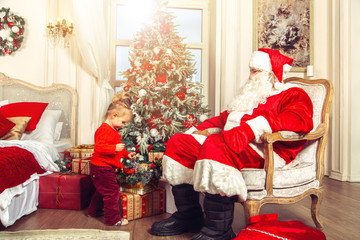 Little cute girl with a real Santa Claus near the Christmas tree.