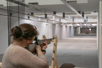 Frau mit Dutt visiert Zielscheibe mit Gewehr an 1