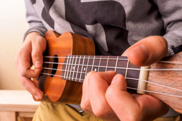 A man playing guitar ukulele in close up view.