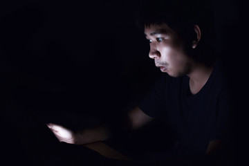 Asian man using smart phone in the black dark room and thinking something