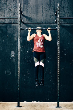 Workout woman pull ups exercise in gym