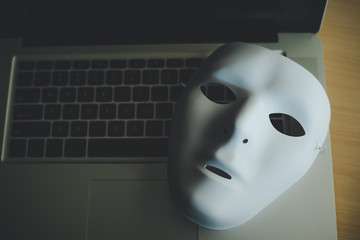 White mask placed on the laptop - concept fraud of social online