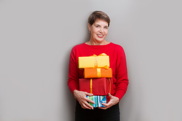 Happy senior lady holding Christmas presents looking at camera and smiling posing about a wall.  Christmas time. Birthday