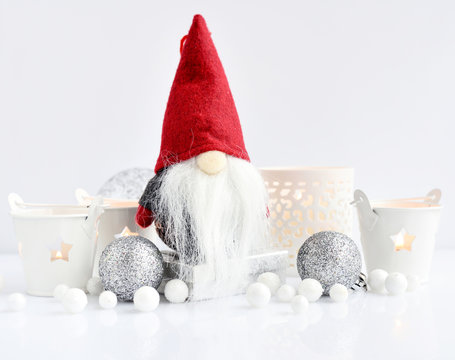 Christmas composition with gnome, candles and festive decorations on a white background. New Year greeting card.