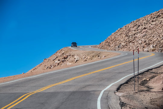 Car rounding sharp bend with steep dropoff on dangerous mountain road with blue sky behind