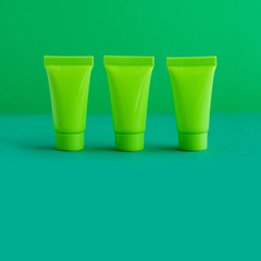 3 three blank green cosmetic tubes on green background. Simple plastic containers, mock up packaging design. shallow depth of field, copy space photography