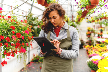 Young florist holding digital tablet
