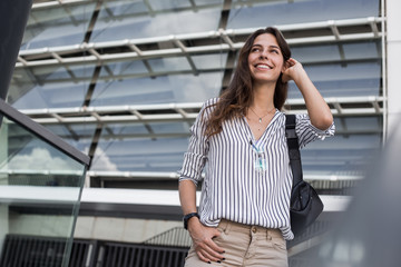 Smilish beautiful stylish woman having good fashion official clothes walking on urban street next to business center with good summer mood. Way to office. Looking for someone and waiting for meet