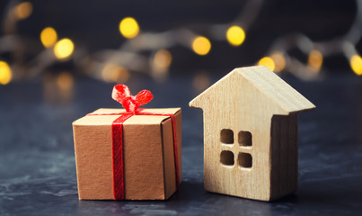 Wooden house and present. Christmas Sale of Real Estate. New Year discounts for buying house. Purchase apartments at a low price. Winter resort and vacation. Holiday discounts