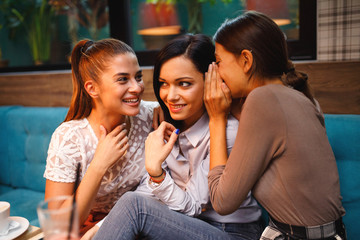 Three young women friends gossip in the cafe