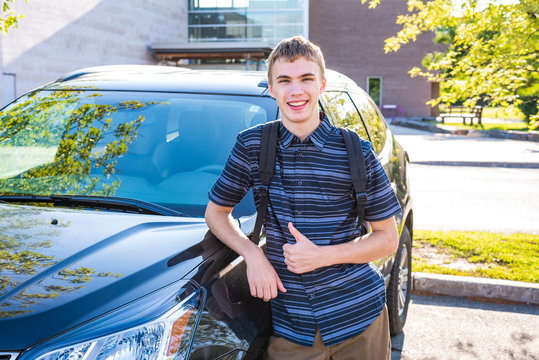Happy male teenager leaning against his car in a high school parking lot.