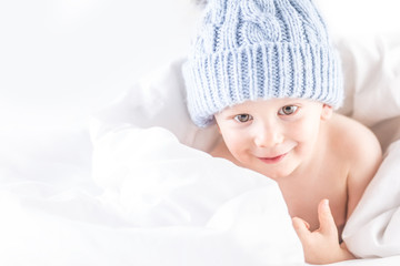 Habby young smilling child boy in white bed