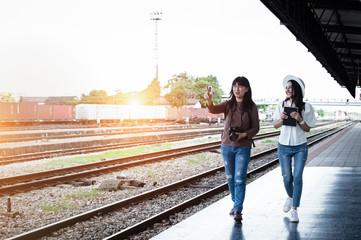 Women traveller walking on platform of railway station,talking together,blurry light around