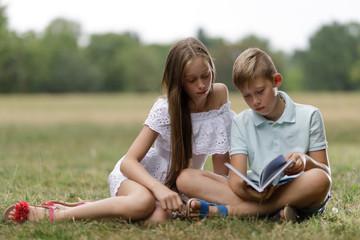 Kinder lesen ein Buch im Park