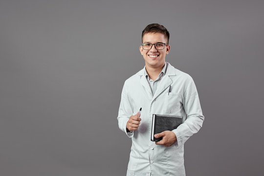 Intelligent smiling guy in glasses dressed in a white coat is holding a notebook and a pan on a gray background